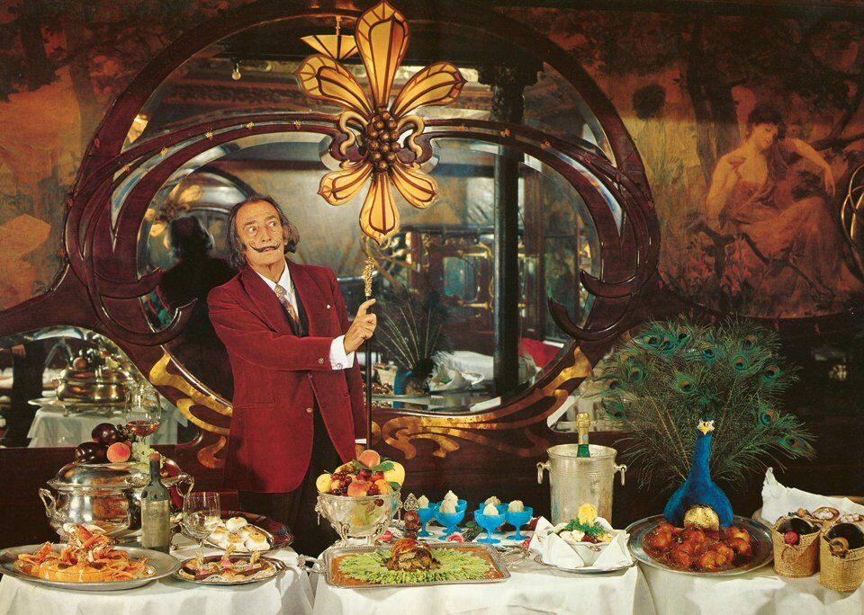 Salvador Dali at one of his lavish dinners. Some of the dishes featured in the photograph appear in his cookbook, <em>Les Dîners de Gala</em>.