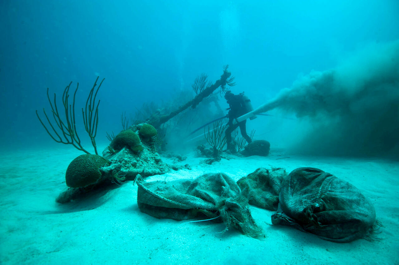 Dr. Philippe Max Rouja, Custodian of Historic Wrecks from the Government of Bermuda, clearing the non-historic layers of sand during the rescue archaeology investigation of the bow of the shipwrecked <em>Mary Celestia</em>, South Shore Bermuda.