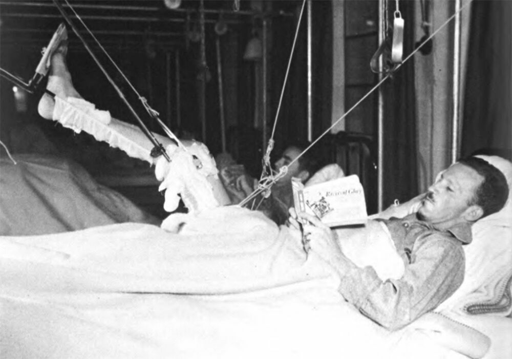 A hospitalized soldier passes the time with an Armed Services Edition.