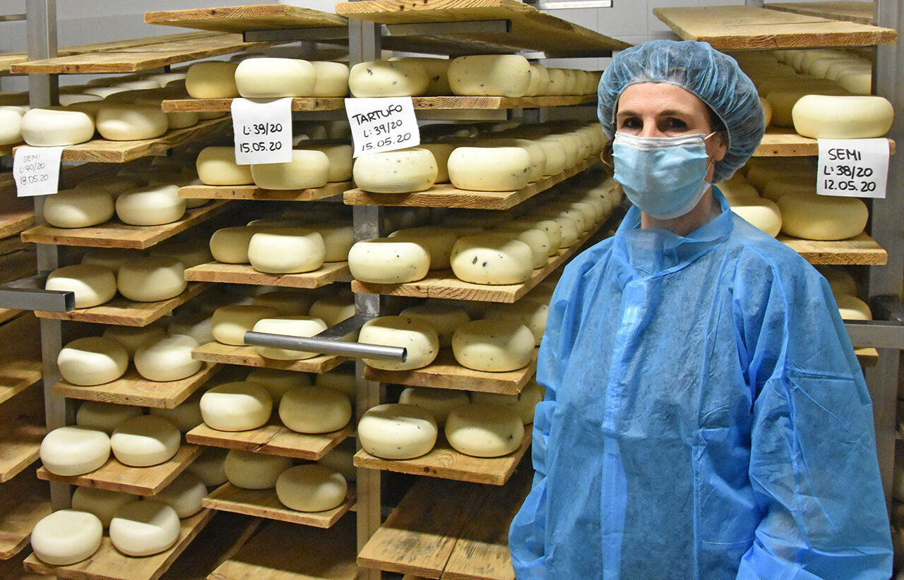 Silvana Cugusi, the daughter of a Sardinian shepherd who migrated to Tuscany in 1962, stands next to cheese wheels.