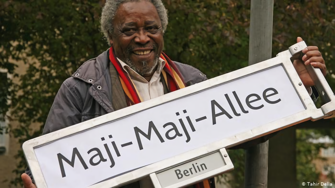 Mnyaka Sururu Mboro, of nonprofit Berlin Postkolonial, holds a sign for a street renamed to commemorate a rebellion in German East Africa.
