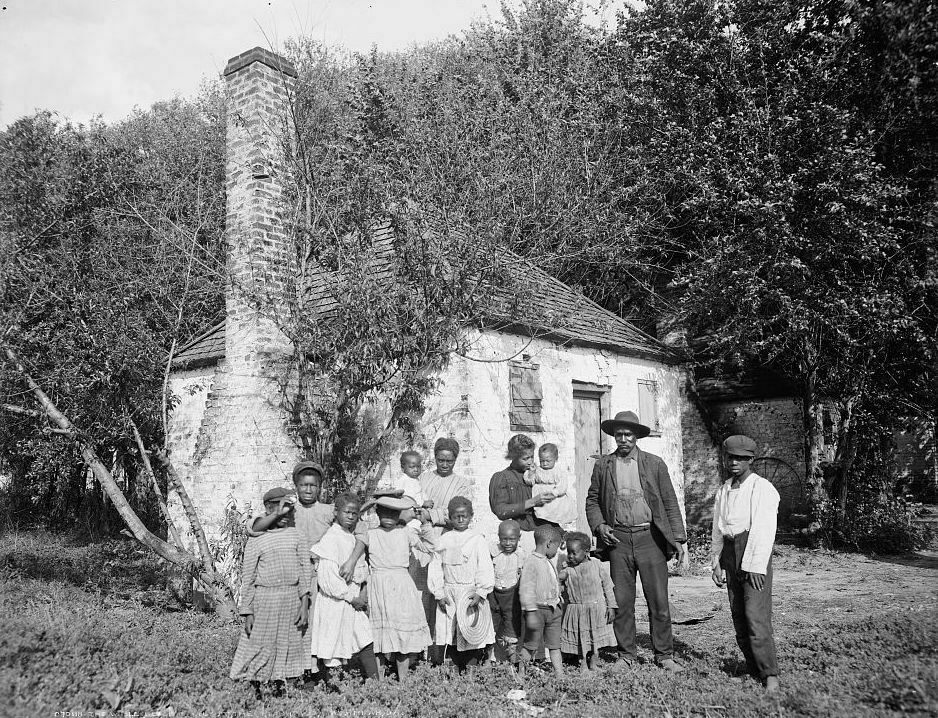An African-American family standing in front of former slave quarters at the Hermitage Plantation in Savannah, Georgia.