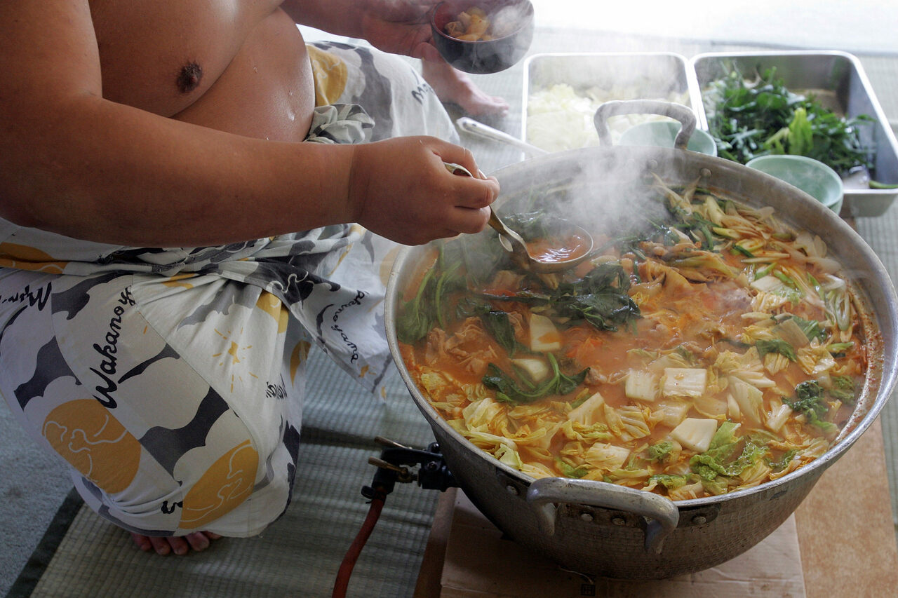 "A sumo wrestler dishes up <em>chanko-nabe</em> during a ""Sumo Diet Campaign"" event in Osaka, Japan."
