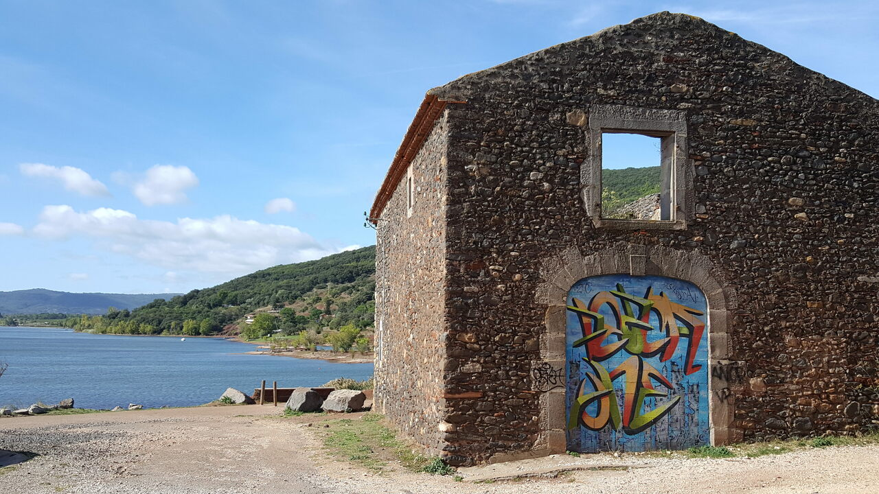 A graffitied former home beside the lake.