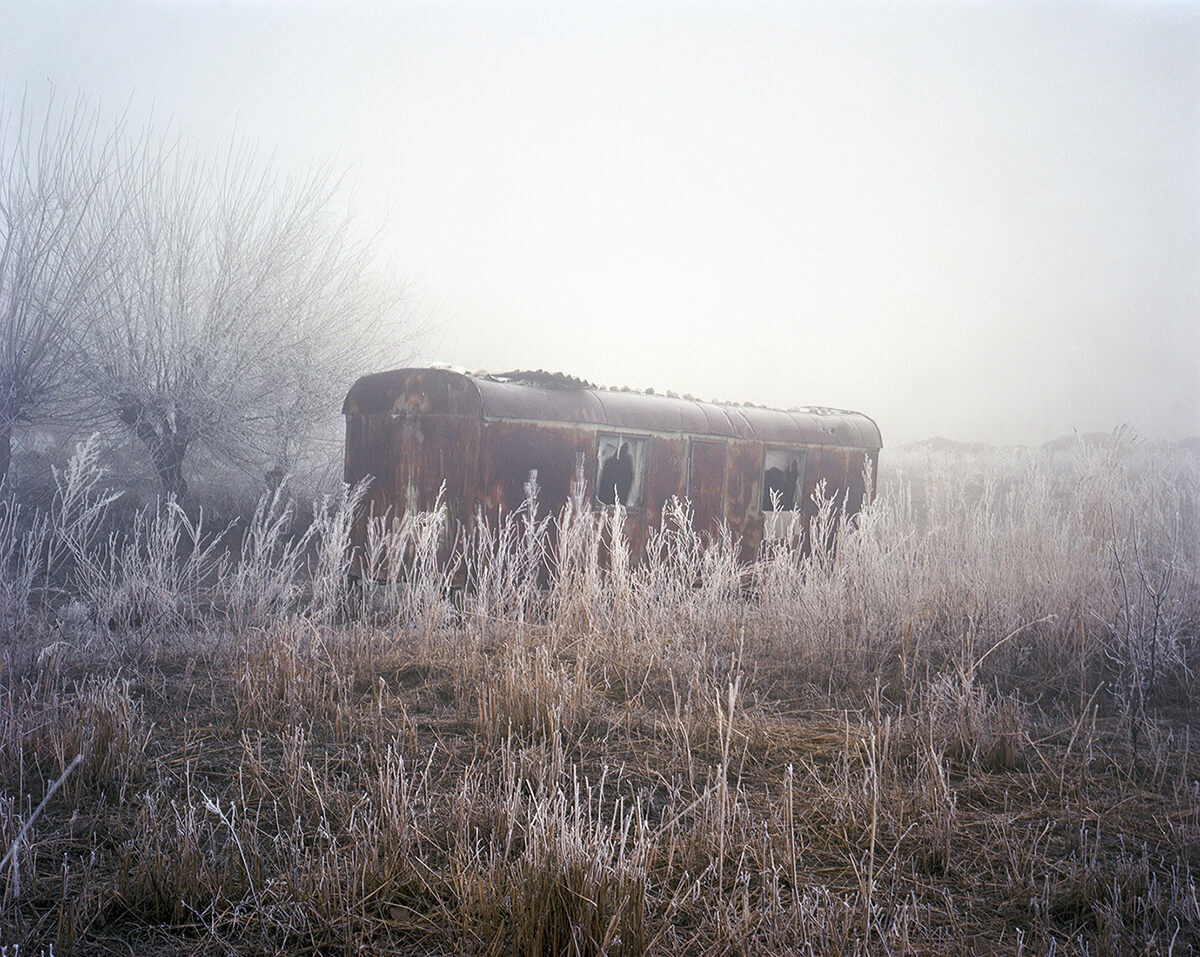 An abandoned trailer in the frost of Mailuu Suu.