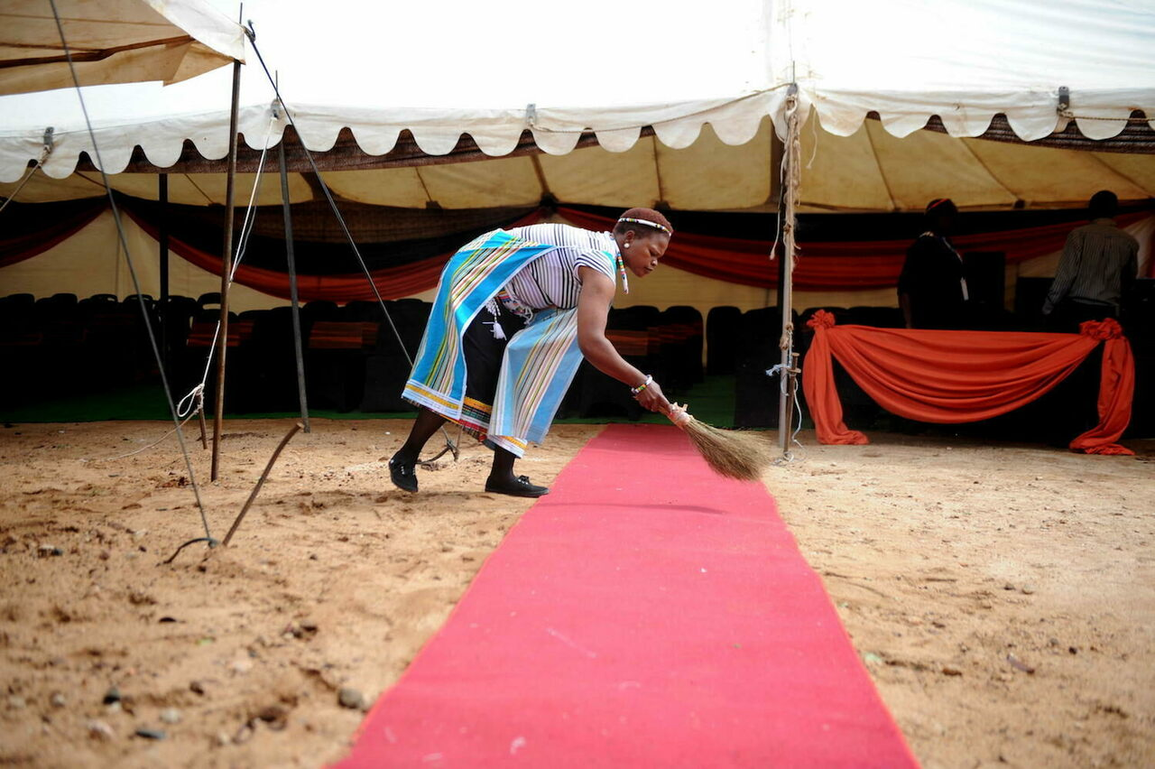 A woman sweeps the red carpet for the annual traditional ceremony for summoning the rains at Queen Modjadji's palace, Limpopo, South Africa, October 13, 2012.