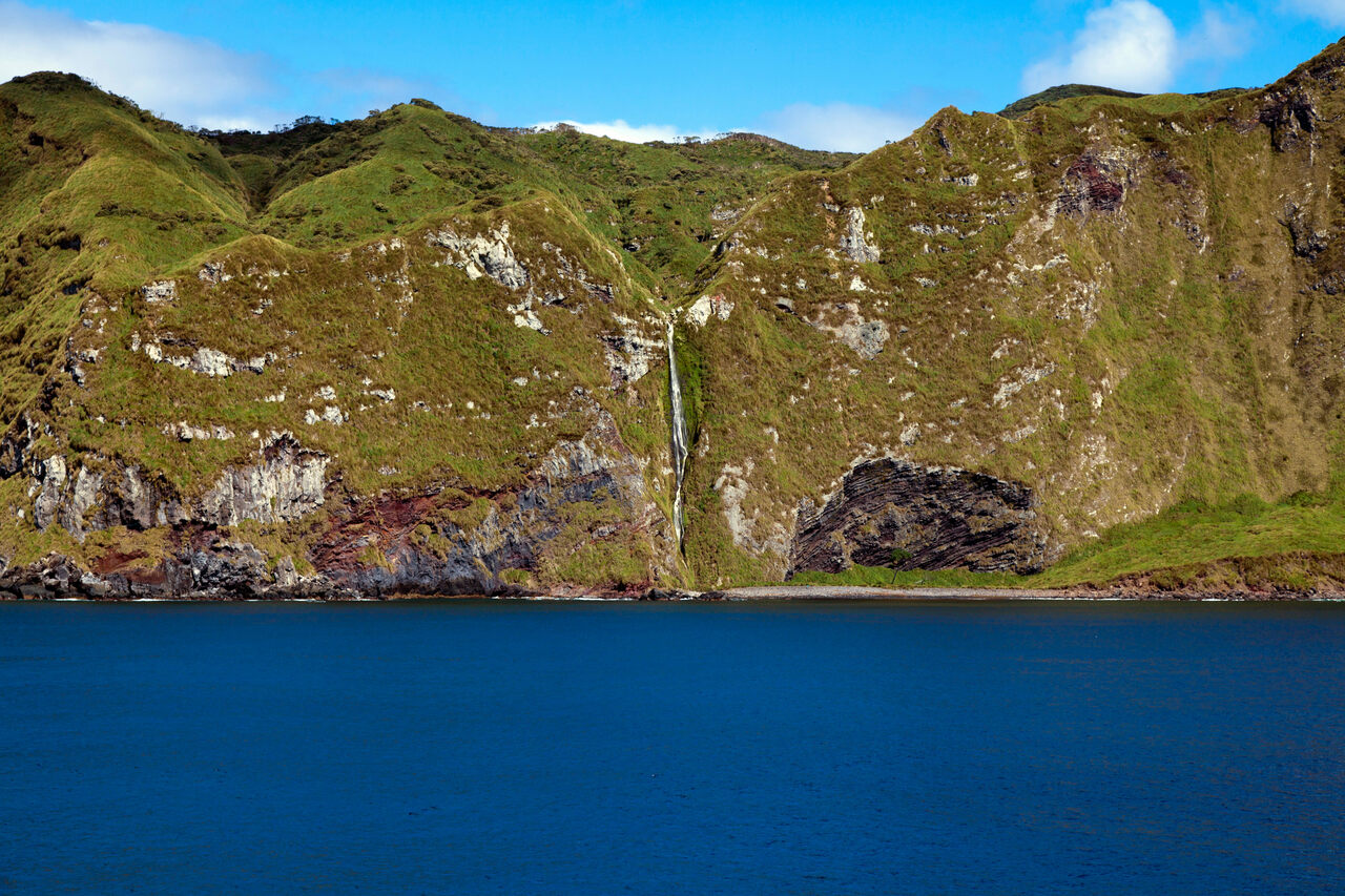 A waterfall cascades down the side of Inaccessible Island.