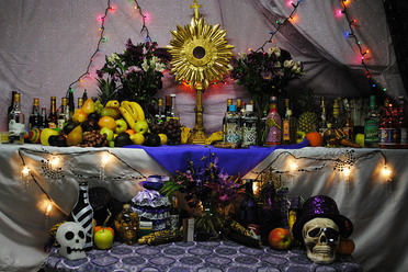 Vodou altar during a celebration for Papa Guédé in Boston. This altar has offerings to three nations (nanchons) of loa: at top right are offerings to Rada spirits; at top left are those for the Petwo family; and those at bottom are for Guédé.