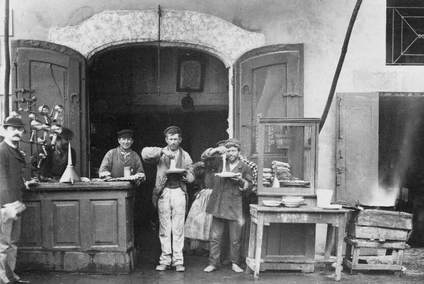 Two men with plates of spaghetti at a street side counter, Naples, late 19th century.