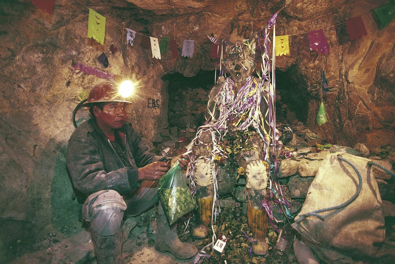 A miner sits at the feet of El Tio, leaving offerings for safety and prosperity.