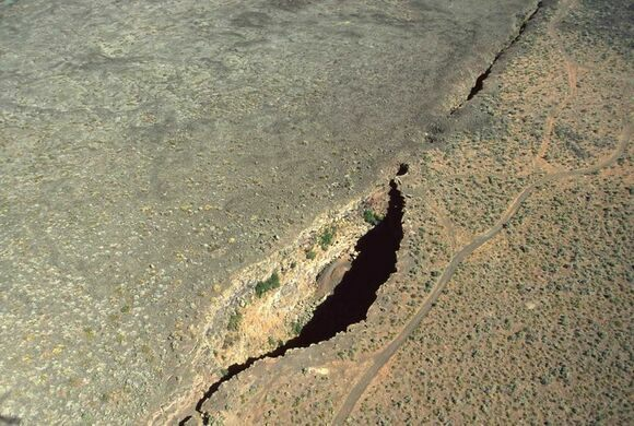 Kings Bowl and Great Rift from air. King's Bowl is a phreatic explosion pit 280 feet (90 m) long, 100 feet (30 m) wide, and 100 feet (30 m) deep, caused by lava meeting groundwater and producing a steam explosion 2,200 years ago. (Wikimedia Commons)