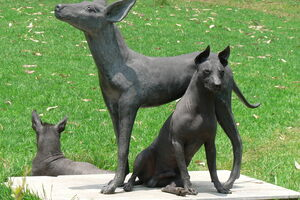 Real dogs next to a statue.