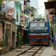 Diesel train coming down the train tracks through a narrow street in Hanoi.