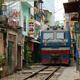 Diesel train coming down the train tracks through a narrow street in Hanoi.