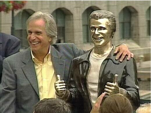 Henry Winkler posing for a picture beside a bronze statue of Arthur Fonzarelli, also known as fonzie, from tv show happy days.