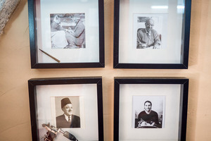 Photographs hang on the shop's wall depicting the last four generations of Razzouk family tattooers: (counterclockwise from top left) Jirius (with hand tool), Yacoub (with early machine), Wassim, Anton.