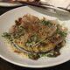 A seafood okonomiyaki topped with bonito flakes
