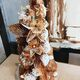 A tower of toffee dough shrouded in toffee and flowers.