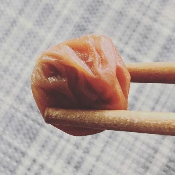 A lone umeboshi between chopsticks.