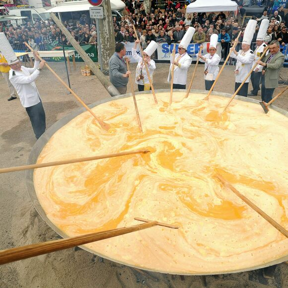 Members of the Giant Omelette Brotherhood stir more than 15,000 eggs on March 28, 2016, on the main square of Bessieres, France.