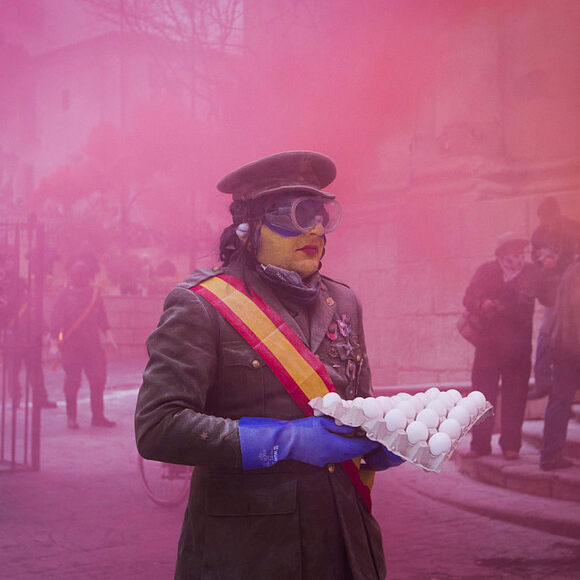 Amidst colored smoke bombs, a mock soldier prepares to throw eggs.