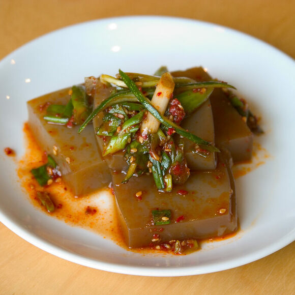 Acorn jelly is often seasoned with soy sauce and sesame oil, and comes topped with green onions, sesame seeds, and Korean chili flakes (gochugaru).