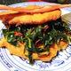 A collard sandwich, with vegan bacon on top.