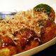 Takoyaki topped with takoyaki sauce, bonito flakes, and aonori (green laver seaweed.)