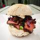 A blaa bread sandwich with steak, onion, mushroom, scallion and horseradish mayo.