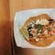 A taco with huitlacoche, pico de gallo, corn, and cheese.