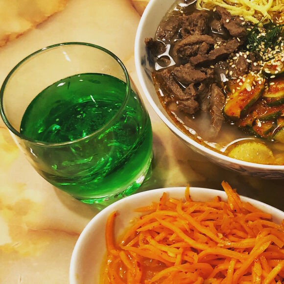 A refreshing glass of tarkhun, with Korean carrots and kuksu soup.