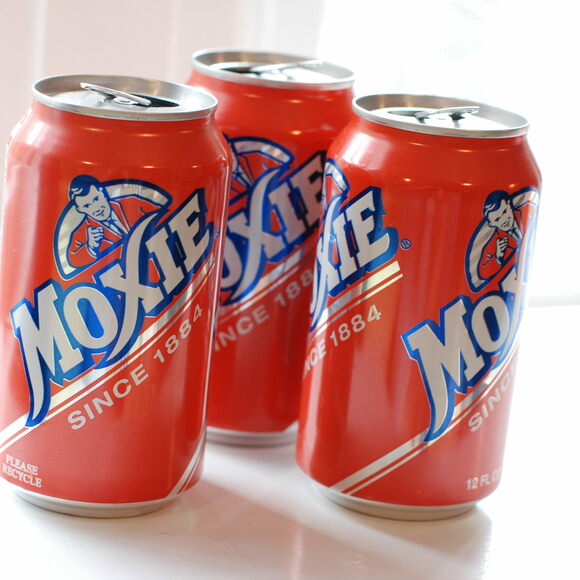 "Cans of Moxie, likened to ""root beer on steroids."""