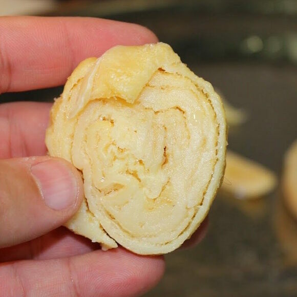 A rolled up ball of sagí, about to be dunked in flour and added to a stew.