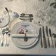 An ice cream fork is pictured (top, closest to the plate) in a Parisian-style table-setting.