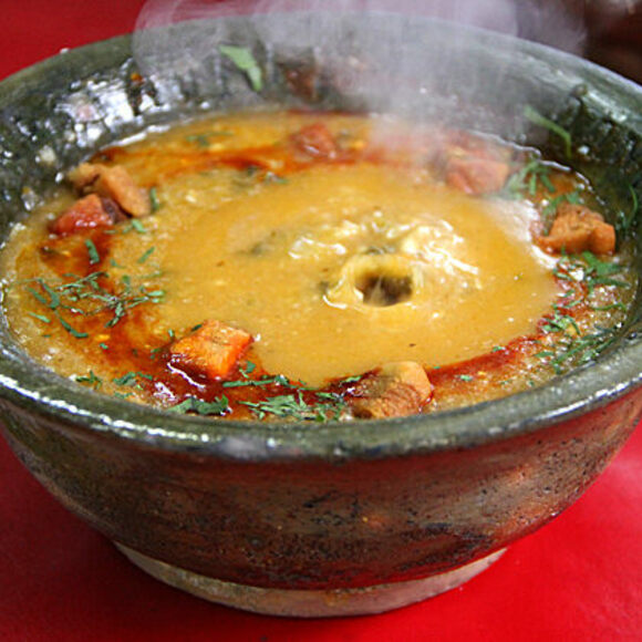 A steaming bowl of k'alapurka, right after the stone was dropped inside.