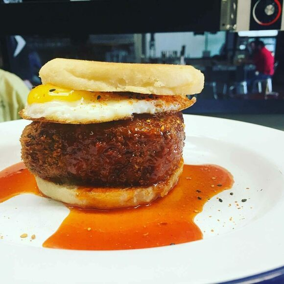 A breaded scrapple and egg sandwich.