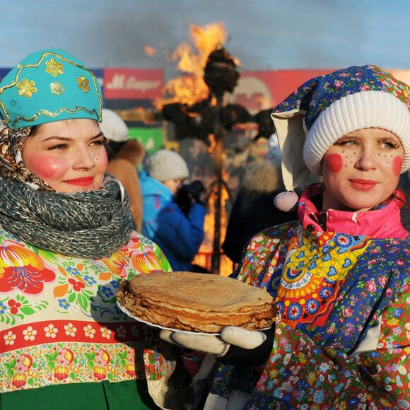 Young women, with blinis, and Lady Maslenitsa burning in the background.