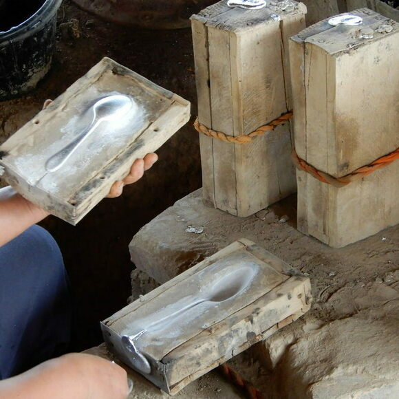When the melted aluminum solidifies inside the wooden mold, the spoon maker pries it open, and removes the spoon.