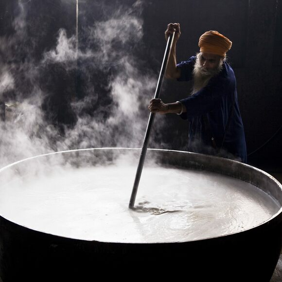 A volunteer cook stirs one of the temple's vats.